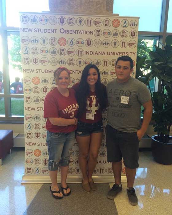 """Three people stand in front of a banner with graphics all over it and the words """"Indiana University New Student Orientation."""""""