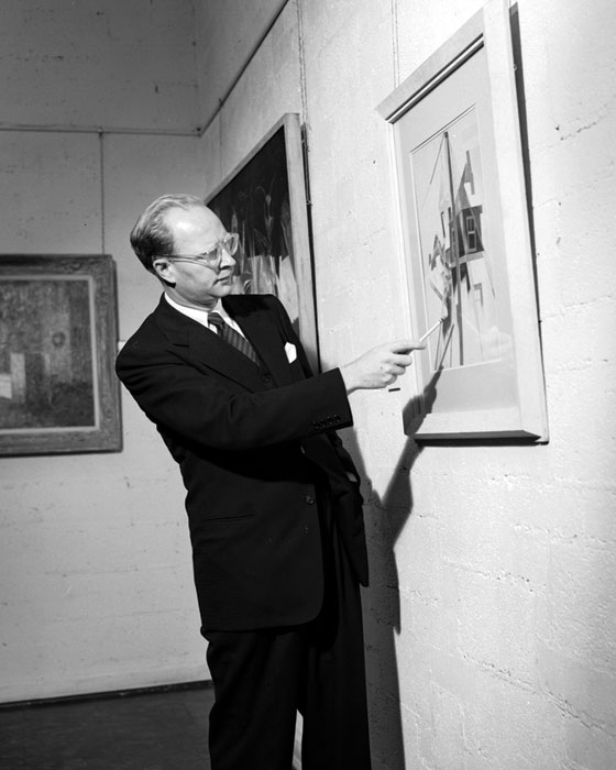 A black-and-white photo of a man wearing glasses and a suit. He is pointing at a piece of framed artwork on the wall.