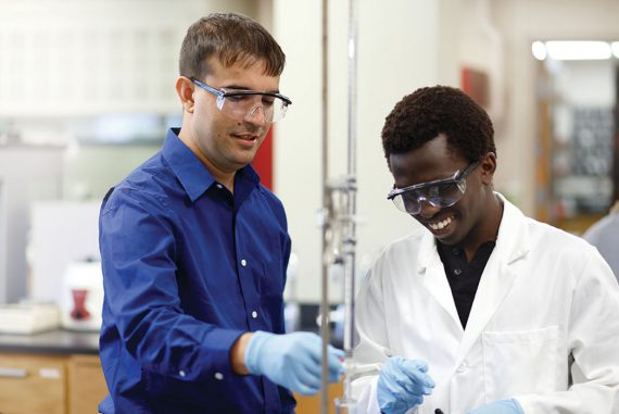 Two men wearing safety glasses work in a lab.