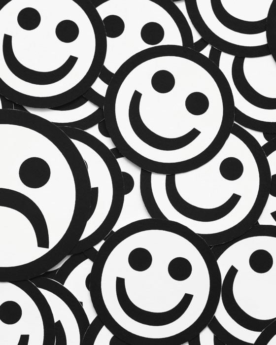 Black and white smiley faces appear as if they're lying in an enormous pile on top of each other.