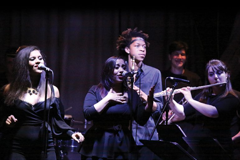 Five members of IU Soul Revue, all wearing black, perform on stage in a dimly lit venue.