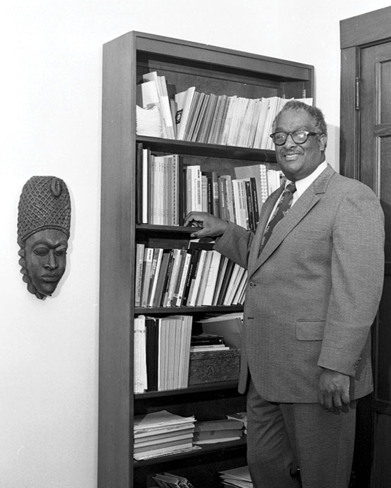 Black-and-white photo of Herman Hudson standing beside a bookcase and an African mask.