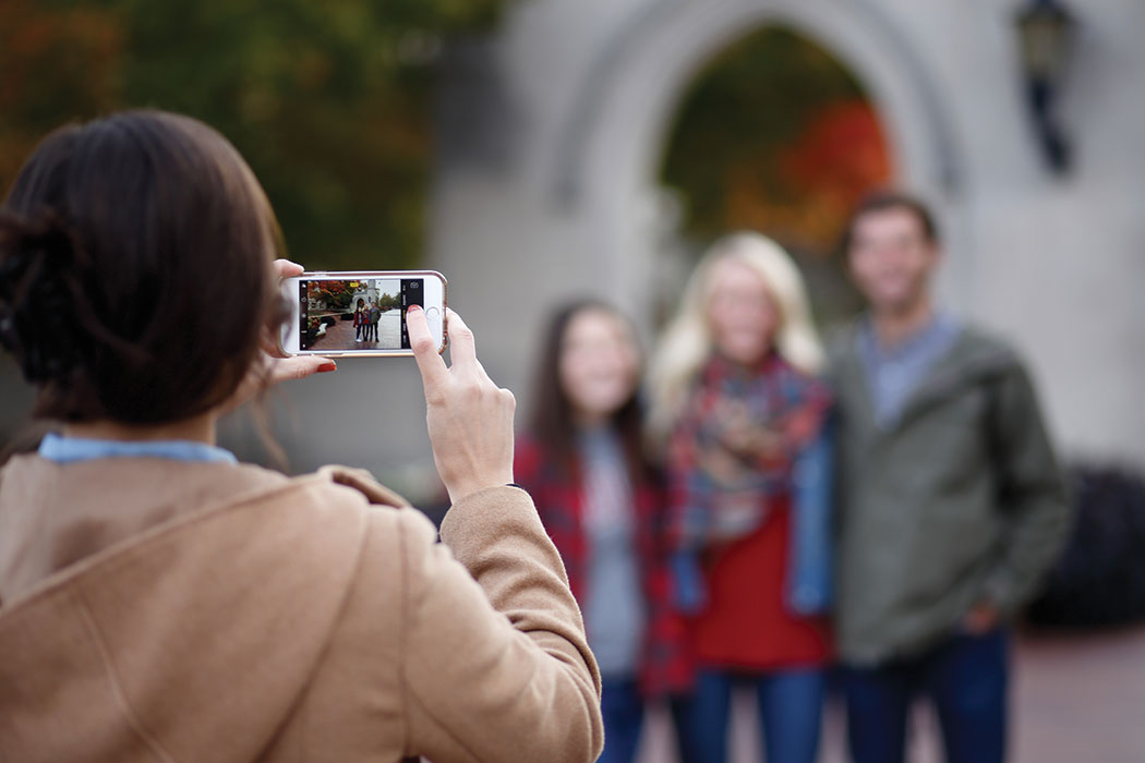 An over the shoulder shot of a woman holding a cell phone and taking a picture of two women and a man posing in front of a building.