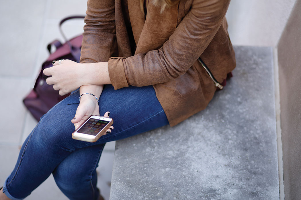 A woman in a leather jacket and jeans holds a cell phone while sitting on a concrete slab. Only her arms from the elbows down, her hands and her thighs are visible.