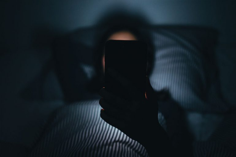 A person lays in her bed in a dark room, her face obscured by the back of a cell phone.