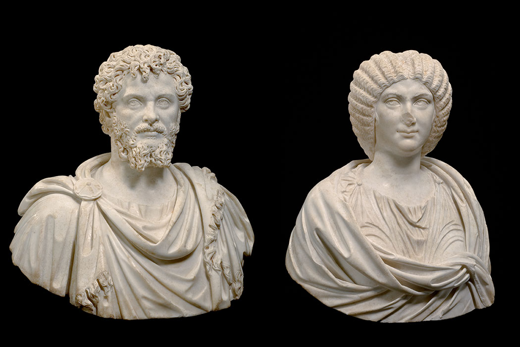Two marble busts, one of a man, one of a woman.