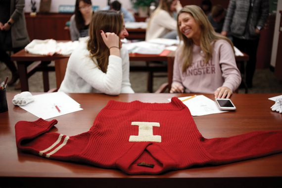 "A red, vintage ""I Man"" sweater lays on a table in the foreground while two female students talk in the background."