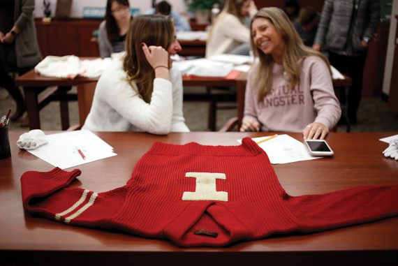 """A red, vintage """"I Man"""" sweater lays on a table in the foreground while two female students talk in the background."""