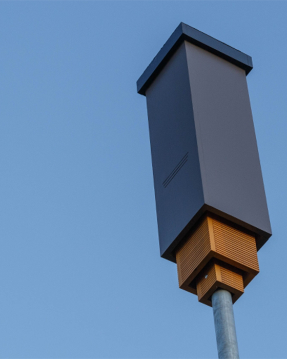 A tall, dark gray box affixed to a metal pole