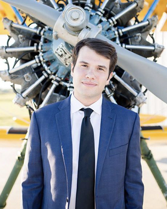 Caleb Blackerby stands in front of small airplane propeller