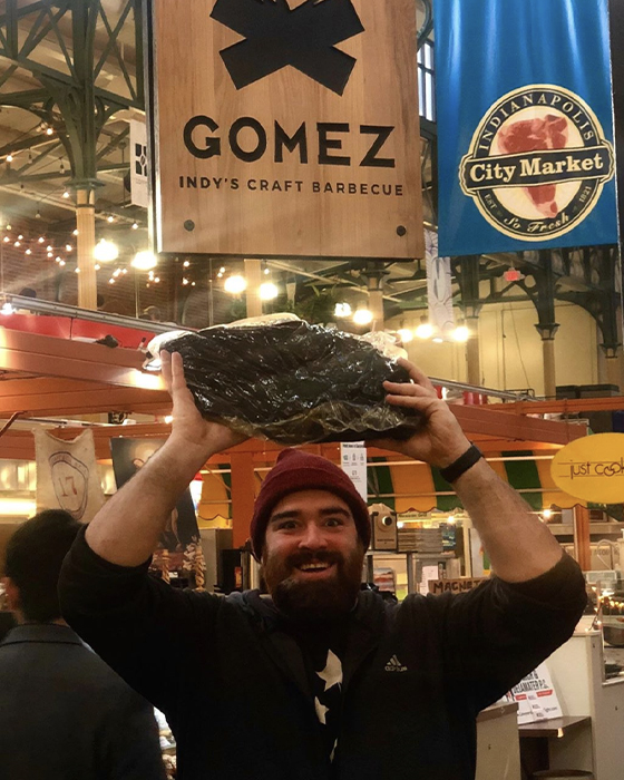 Michael Gomez holds huge chunk of meat above his head