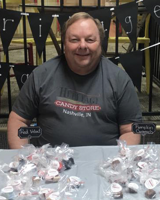 Greg Percifield sits behind candy table