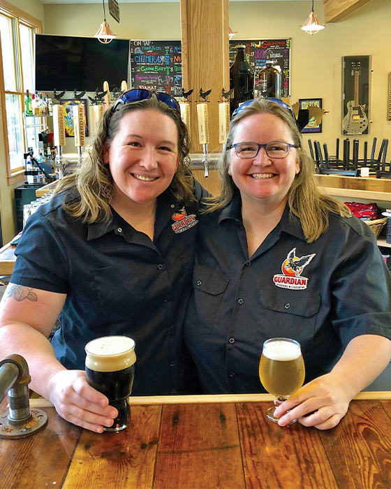 Kim Collins and Kate Bishop stand behind Guardian Brewing Company bar with beer in hand