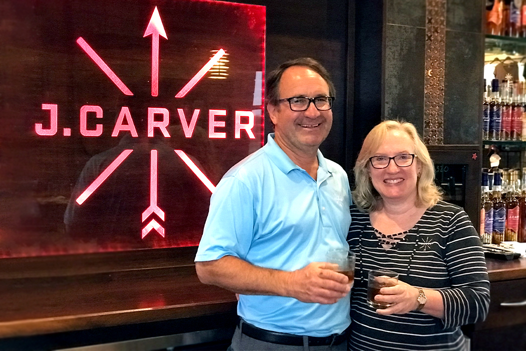 Bill Miller and wife stand at J. Carver bar and hold drinks