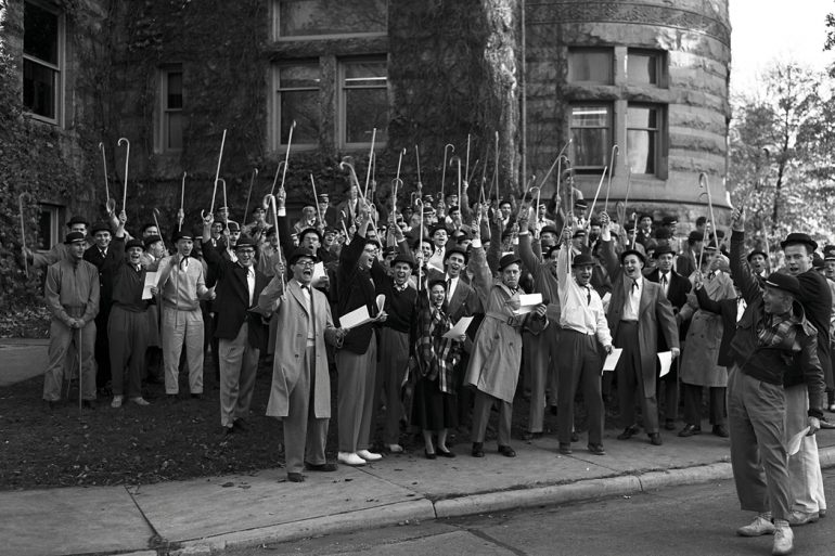 Black-and-white photo of a large group of male students in suits and hats. They are holding canes and raising them in the air as they shout.