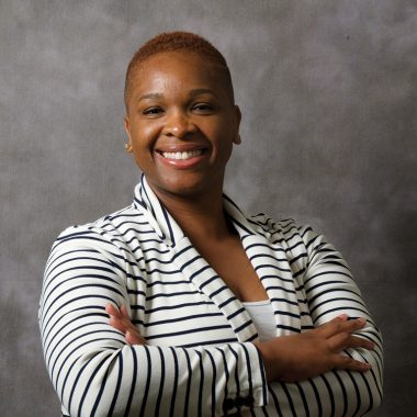 A woman with brown skin and short, cropped hair smiles broadly. She wears and black-and-white striped blazer and has her arms crossed at her chest.