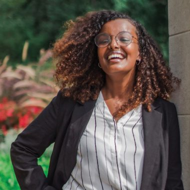 A woman with brown skin and shoulder-length, curly, brown hair lifts her chin to the side and smiles broadly. She is wearing a black blazer over a white button-up shirt with pinstripes. She has a nose ring, small hoop earrings, and round, metal-framed eyeglasses.