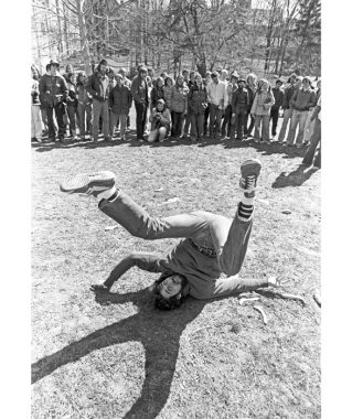 Black-and-white photo of a man with shaggy, dark hair and a thick mustache laying on the ground with his arms splayed beneath him and his legs in a V in the air. A crowd of onlookers watches from a distance.