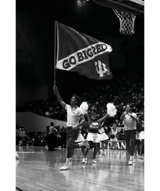 "A male cheerleader runs across a basketball court carrying a flag that has a trident on it and the words ""Go Big Red."""