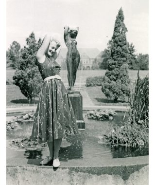 Black-and-white photo of a smiling woman with shoulder-length blonde hair. She wears flat, lace-up shoes and a sleeveless, below-the-knee dress that's belted. The woman has her arms crossed behind her head, mimicking the pose of the nude female statue in the garden behind her.