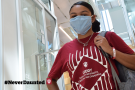 A student with medium-brown skin wearing an IU shirt and light-blue face mask holds onto the strap of their backpack and looks at the camera.