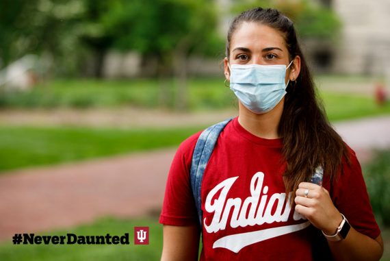 A student with brown hair in a ponytail, and wearing a red Indiana T-shirt and a light-blue face mask, walks through the Bloomington campus.