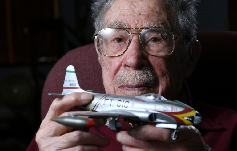 Centenarian Oliver G. Cellini holding a model airplane.
