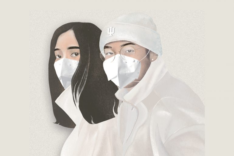Two people with dark hair wearing all-white clothing, including white face masks, stand close together and look forward. The person on the right wears a white beanie with an IU trident on it.