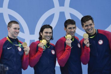 Four men wearing matching warm-up jackets stand shoulder to shoulder, smiling while holding up their Olympic gold medals.