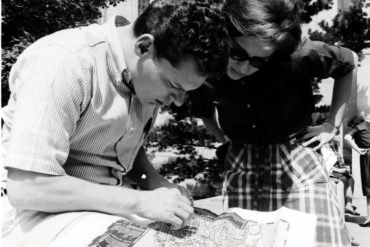 In this black-and-white photo, a male student and female student hunch over a campus map to study their whereabouts.