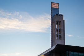 A wide-shot photo of the IUPUI bell tower picutured against a blue sky.