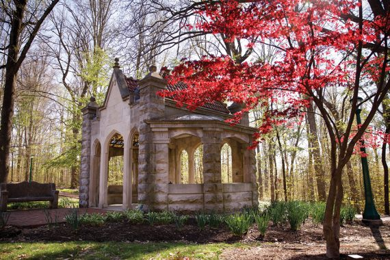 The limstone Rose Well House is pictured on a sunny, fall evening behind a tree of red foliage.