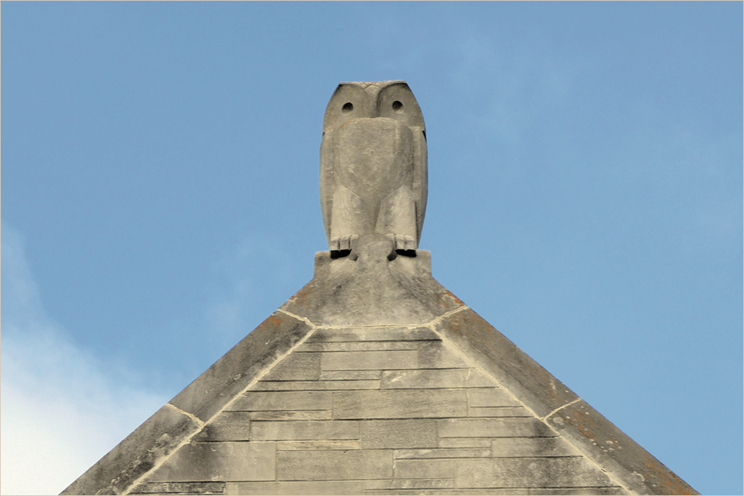 A limestone sculpture of an owl sitting on the peak of a roof.