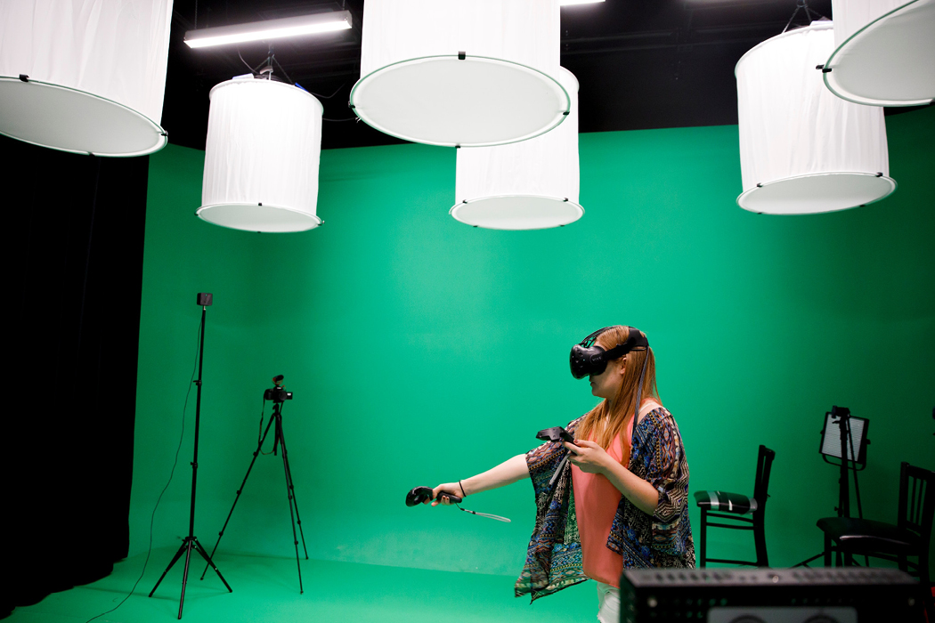 A person with long, strawberry-blond hair wearing a headset and using hand controller stands in the middle of a green-screen room with various equipment, like cameras and special lights.