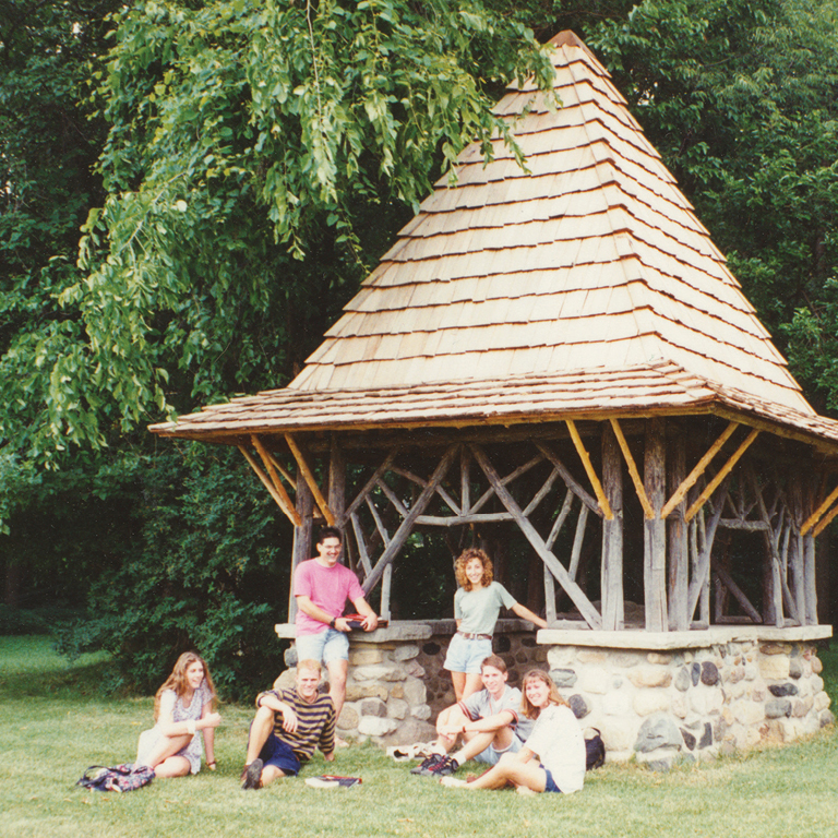 A group of six students pose in front of the Well House (a structure with a stone base, open frame of natural wood, and peaked roof of shingles) which sits along a thicket of trees.