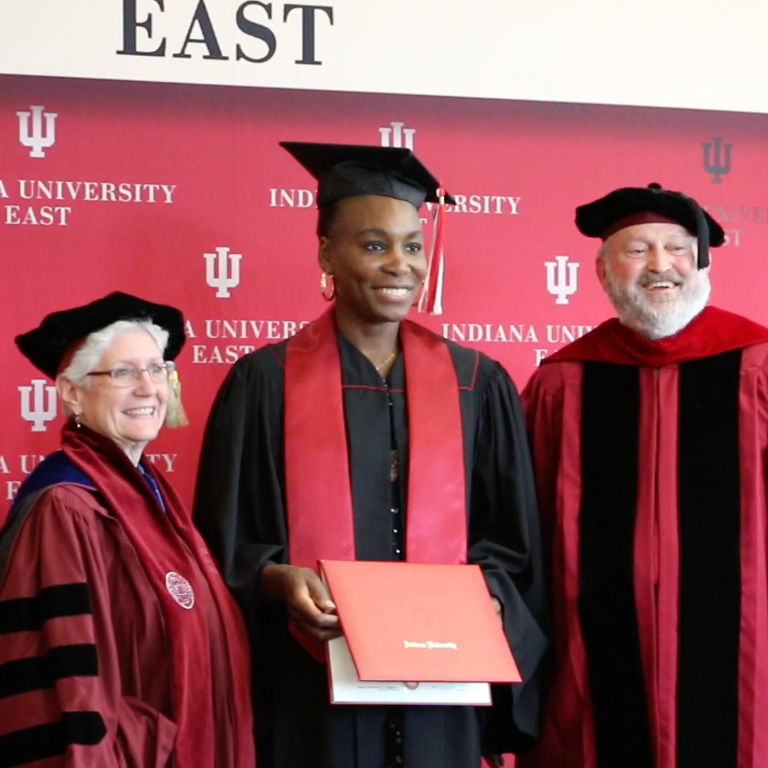 Venus Williams, a tall Black woman wearing a graduation cap with tassel, black graduation robe with red stoll, and holding a red diploma holder. On either side of her are an older white woman and older white man wearing academic regalia.