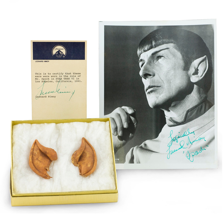 Two tan, pointy-tipped ears sit in a lined, golden box next to a signed photograph depicting Leonard Nimoy as the character Spock, and a certificate of authenticity from Paramount.