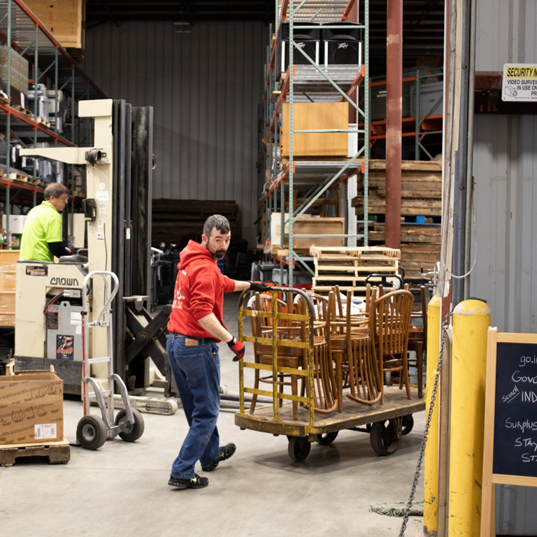 Two people in a warehouse moving furniture.