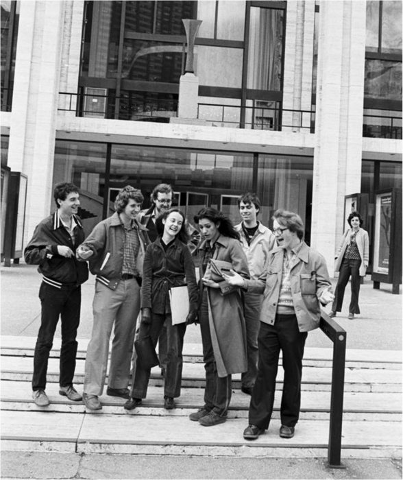 Black-and-white photo of seven college students in early 1980s garb, standing on steps in front of a building with a glass facade.