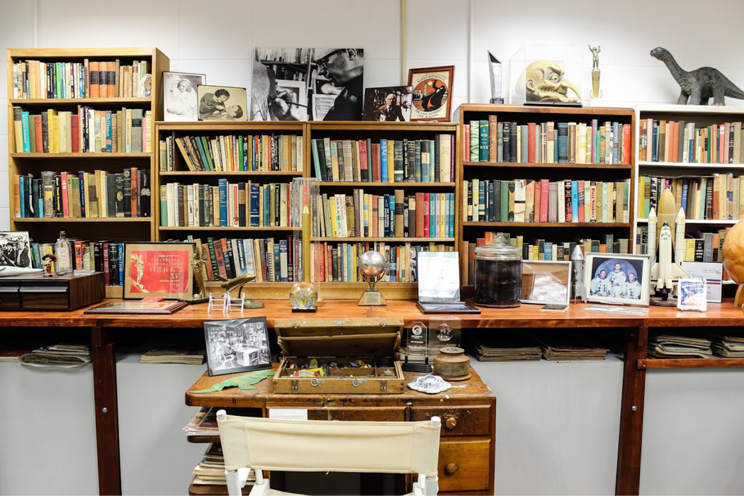Wooden shelves packed with books and other ephemera, such as a miniature dinosaur, monster mask, framed pictures, awards, and more.