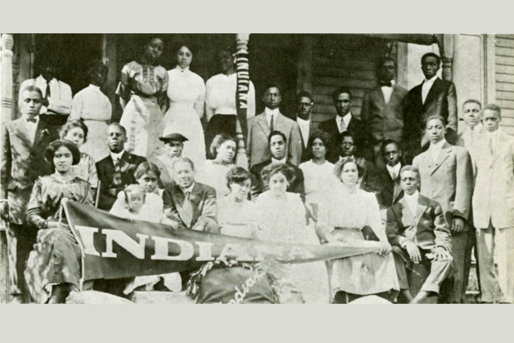 "A sepia-toned photograph of a group of Black men and women standing in three rows on the porch of a house. The people in the front row hold a large ""Indiana"" pennant."