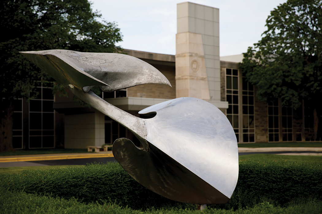 A silver sculpture that looks somewhat like a spade atop the grass, tilted 45 degrees, with a pointy beak affixed to the top.