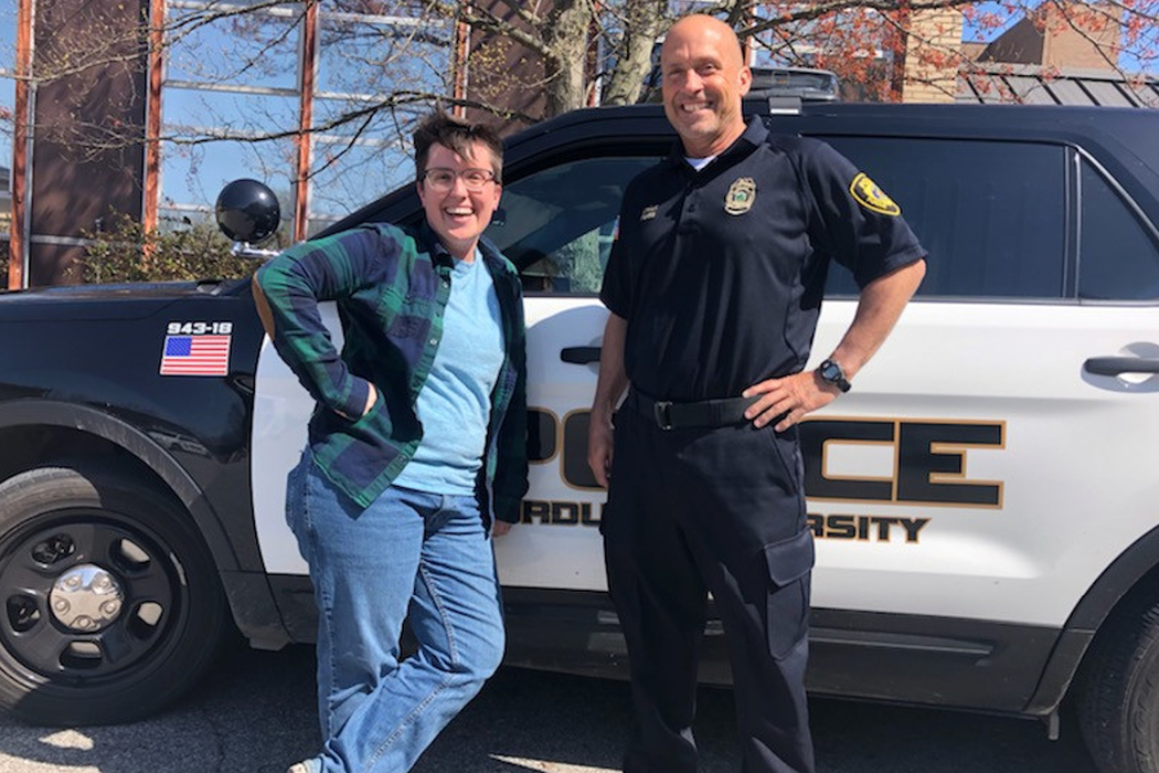 Two people stand in front of a police vehicle. On the left is a person with short brown hair, wearing glasses; an unbuttoned, long-sleeve, blue-and-green plaid shirt over a light-blue T-shirt; blue jeans; and sneakers. They have their right hand on their hip and they're leaning against the vehicle. The person on the right is bald and stands with his left hand on hip. He wears a black, short-sleeve, collard shirt with a police logo on it; black cargo pants; and black shoes.