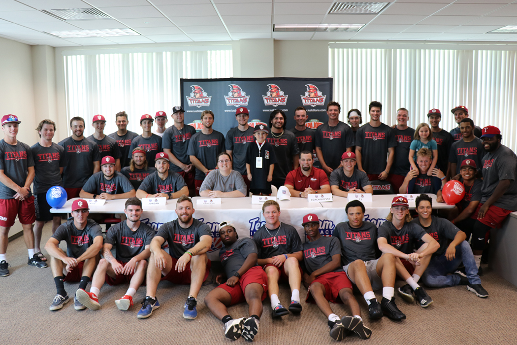 """A group of college baseball players wearing """"Titans"""" T-shirts and red I-U baseball caps surround a long table where a small, smiling boy in an oversized Titans shirt stands on a chair."""