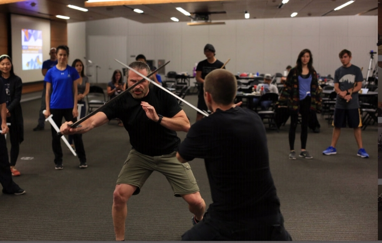 Patrick Kelly crosses swords with a student in class