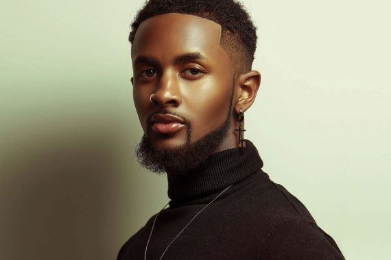 A Black man with a nose ring and a black cross earring, wearing a black turtleneck looks forward with determination in his eyes.