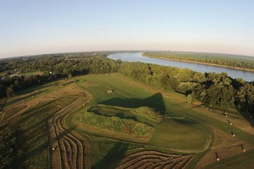 Aerial photograph of the Angel Mounds State Historic Site on a sunny day. At center is a large Earth mound surrounded by woodlands and bordered on the south by the winding Ohio River.