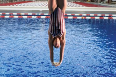 Photograph of a female diver, upside down in mid-dive, wearing a red-and-white striped IU swimsuit. The IU swimming pool and facility can be seen in the background.