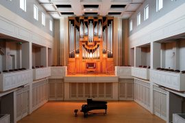 Photograph of a pipe organ built into the wall on a stage in an intimate theater setting.
